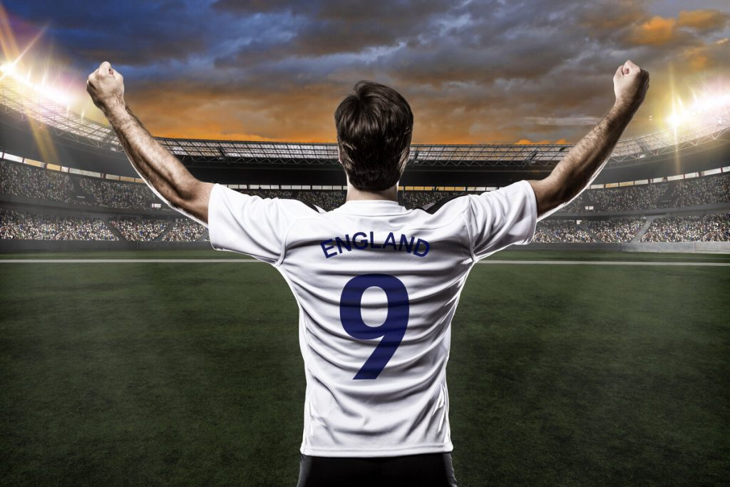 An England footballer with number 9 shirt facing an empty stadium