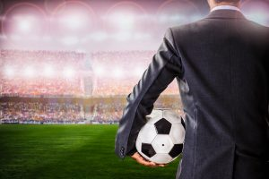 A football manager on the touchline holding a ball