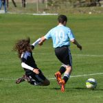 A youing footballer making a tackle