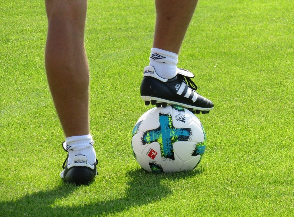 A footballer with his foot on the ball